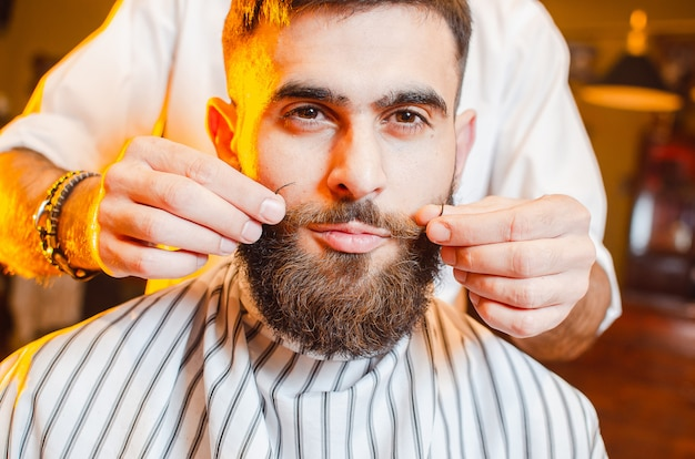 理容師はスタイリングの口ひげを作る
