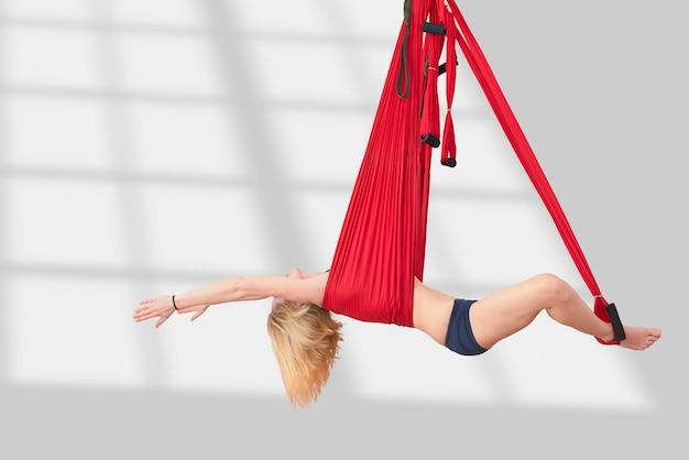 フライヨガ。女の子はハンモックで空中ヨガに取り組んでいます。フィットネストレーニングホワイトジムロフト教室