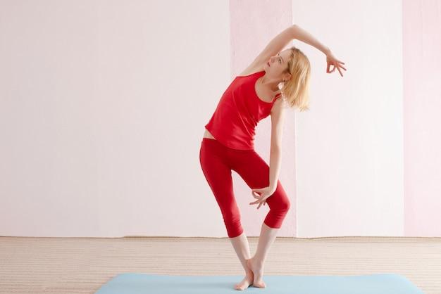 女の子はスタジオで赤いスポーツウェアでヨガを練習しています。ヨガのポーズ。コピースペース