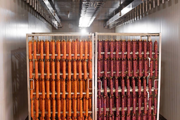 Сушеная колбаса висит на веревке на металлическом каркасе в коптильне.
