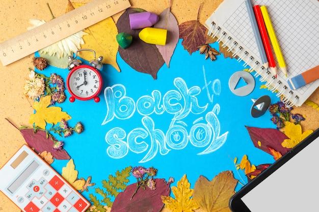 学用品と古い目覚まし時計と秋の乾燥した葉のフレーム。