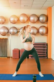 Молодая беременная женщина танцует
