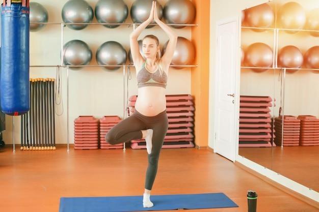 Молодая беременная женщина занимается йогой
