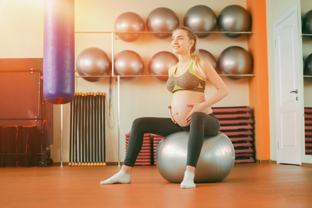 Молодая красивая беременная женщина в спортивной одежде, занимаясь йогой и поглаживая живот