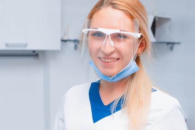 Портрет молодой женщины стоматолог в офисе