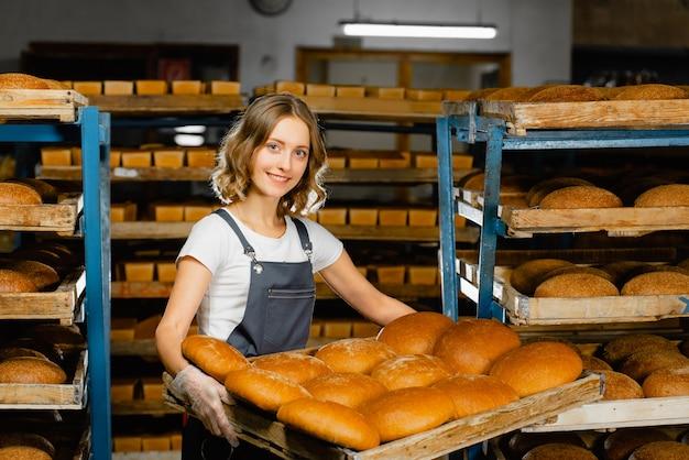 Женщина-пекарь держит поднос со свежим горячим хлебом в руках