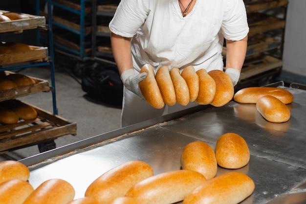 Хлеб в руках пекаря. горячий запекать из духовки. промышленное производство хлеба
