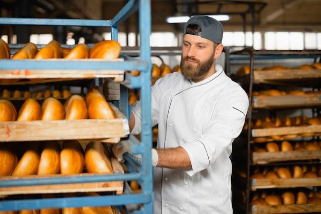 Пекарь несет в пекарне полку с хлебом. промышленное производство хлеба