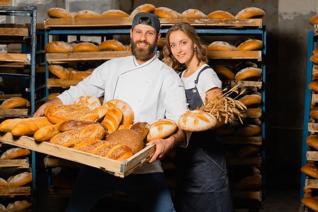 Пекари держат деревянный поднос с ассортиментом хлеба