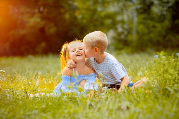 美しい子供たちは夕日の光線で緑の芝生に座る