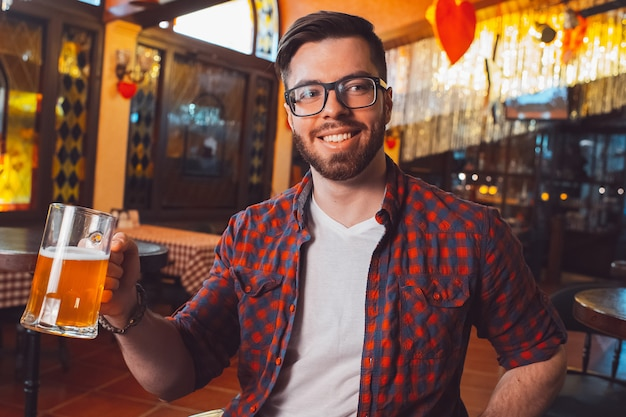 彼の手で泡立ったビールのグラスとメガネの若い魅力的な男