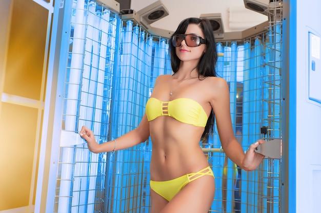 サンルームの女の子。サンルームでの日焼け。医療美容センターでの光線療法の手順