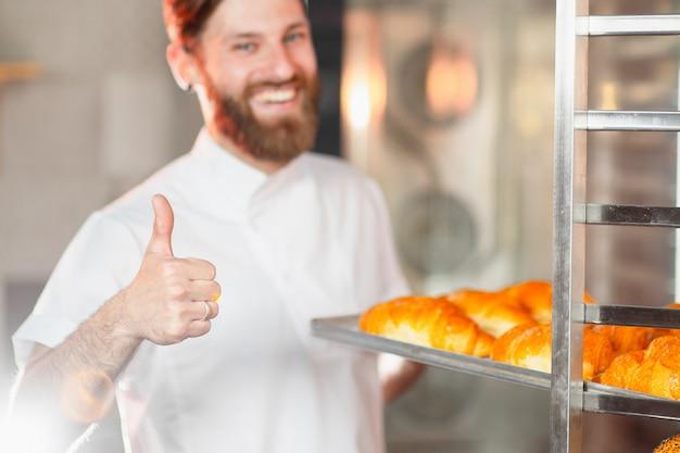 若いハンサムなパン屋は彼の親指を現しています