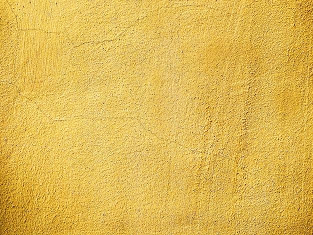 き裂を有する漆喰の古い壁のテクスチャは黄色に塗られました。空のグランジ背景