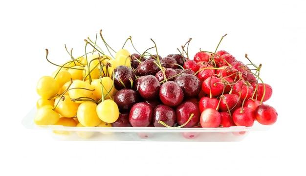 Вишни разных видов и цветов с каплями воды. здоровая пища изолирована