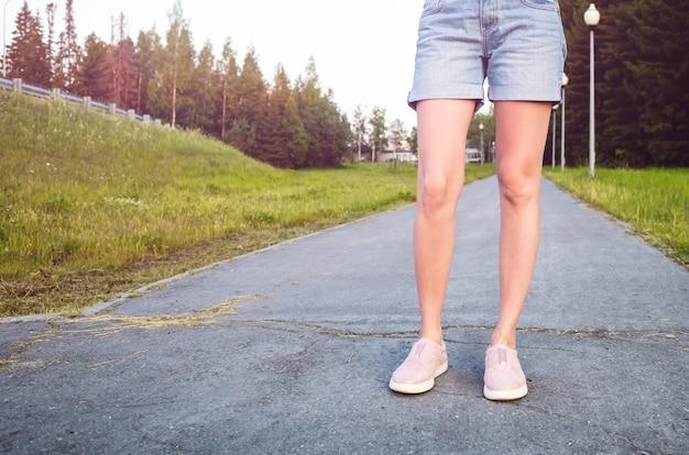 歩道に青いデニムのショートパンツとピンクのスニーカーの女性のスリムな脚。