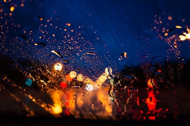 Яркие огни ночного города сквозь стекло в каплях дождя.