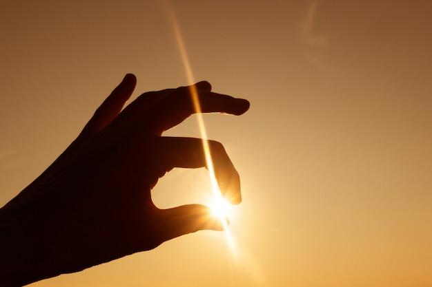 夕日に対する手のシルエット。指の間の光線と太陽。