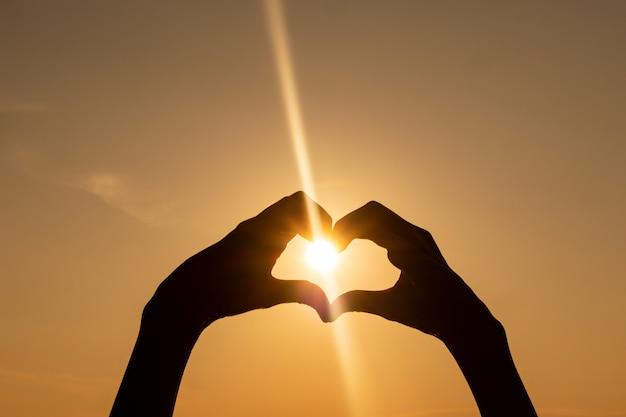 夕日を背景にシルエット-ハートの形に折り畳まれた手。
