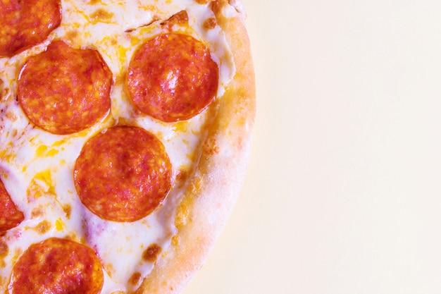 黄色の背景にペパロニのピザ。