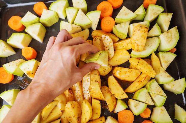 焼き野菜を調理するプロセス。天板には、ズッキーニ、ニンジン、ポテトがスライスされています。