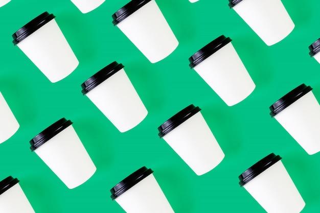 飽和緑に黒の蓋が付いたホワイトペーパーのコーヒーカップから明るい効果。