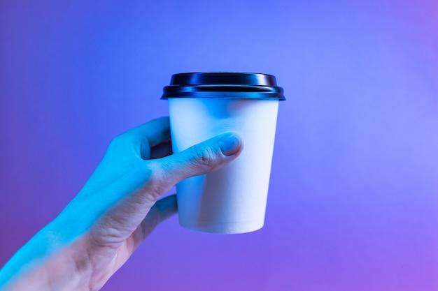 トレンディなネオンの光の手で紙のコーヒーカップ。
