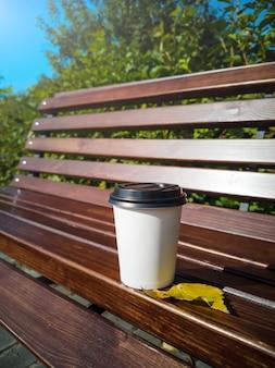 Бумажная кружка кофе стоит на деревянной скамье в парке на солнечный день.