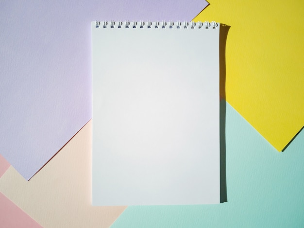 色紙の白いページとスパイラルに空白のメモ帳。トップビュー、ミニマリズム、フラットレイアウト。