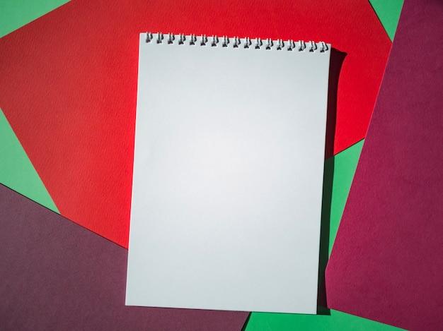 Пустой блокнот на спирали с белыми страницами на цветных листах бумаги. вид сверху, минимализм, плоская планировка.
