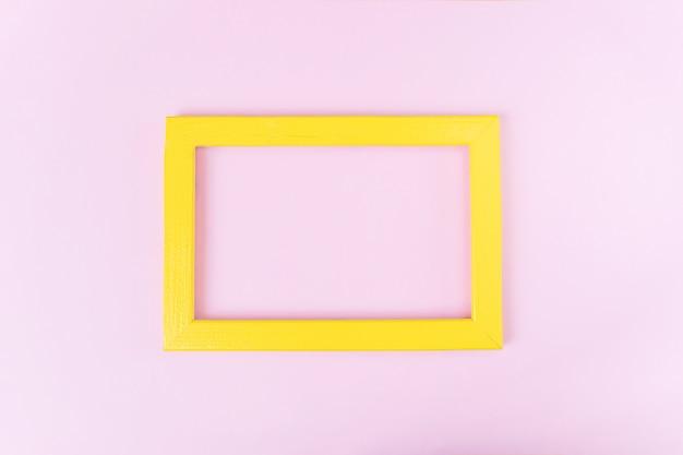 Желтая деревянная пустая фоторамка на розовом