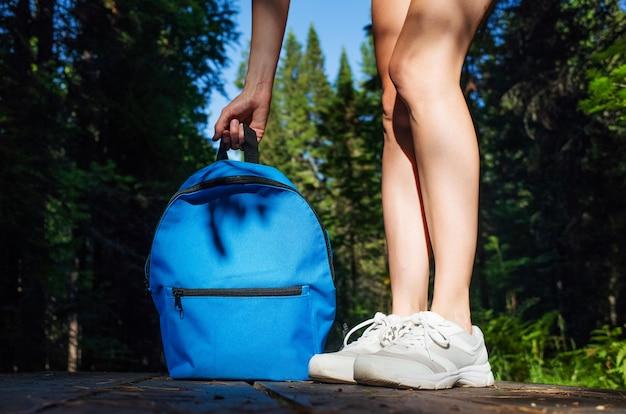 森の木の道に青い小さなバックパックの横にある白いスニーカーの女性の足。