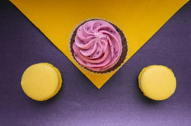 Фиолетовый кремовый кекс на желтой салфетке и желтый макарон на синем
