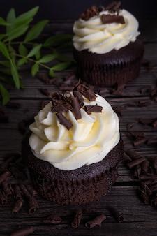 Шоколадные кексы с белым кремом и шоколадной стружкой на деревянном фоне