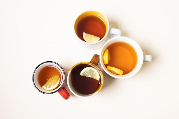 Чашки с чаем с лимоном на бежевом фоне.