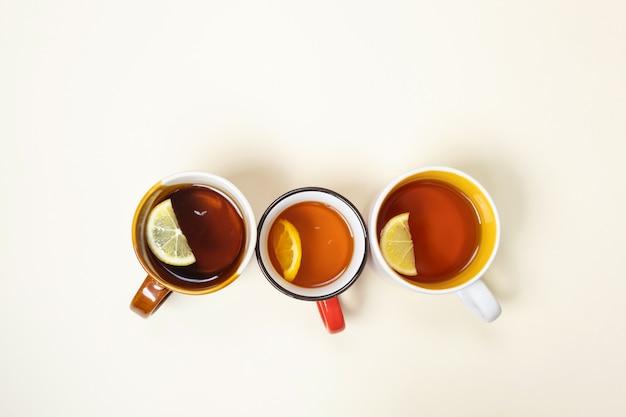 ベージュ色の背景にレモンとお茶のカップ。