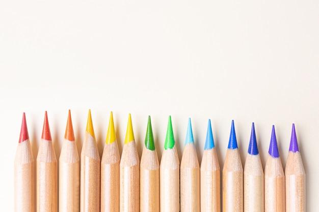 Карандаши цвета радуги расположены в ряд. светло-бежевый фон, копия пространства. красный, оранжевый, желтый, зеленый, голубой, синий, фиолетовый.