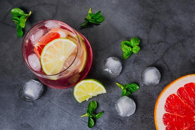 Цитрусовый холодный коктейль в прозрачных очках на темном фоне