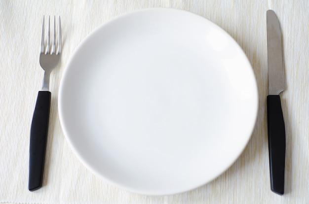 Пустой белый блюдо нож и вилка бежевая салфетка