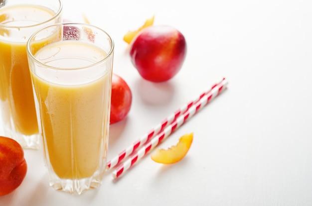 Сок из персиков и нектаринов с мякотью со свежими фруктами на белом фоне.
