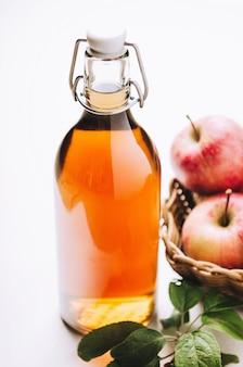 りんごと白い木製のテーブルの上の瓶にリンゴ酢。素朴なスタイル