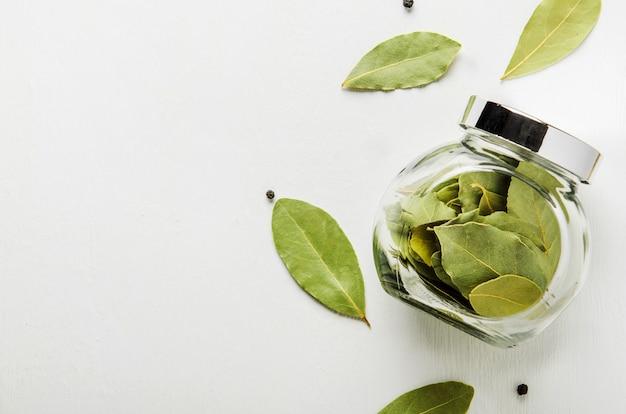 白い背景の上の乾燥月桂樹の葉。スパイス用のガラス瓶。