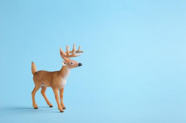 青色の背景におもちゃの鹿