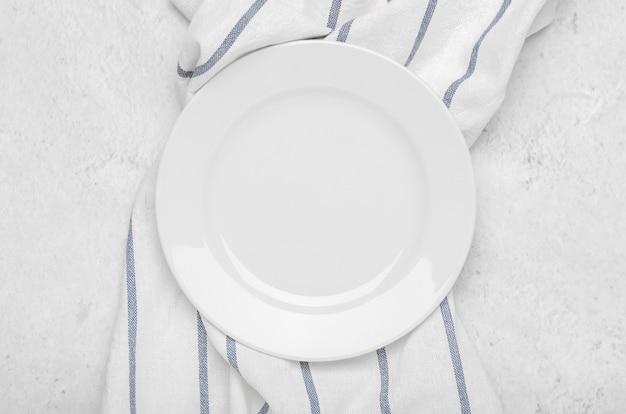 Чистая белая тарелка на свежем полотенце с полосками на каменном светлом минималистском фоне.
