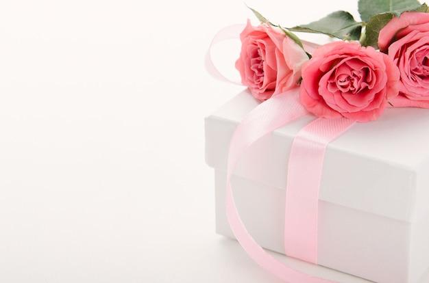 Белая подарочная коробка с розовой лентой и розы на белом фоне.