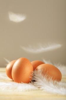 Куриные яйца с развевающимися белыми перьями на деревянном фоне