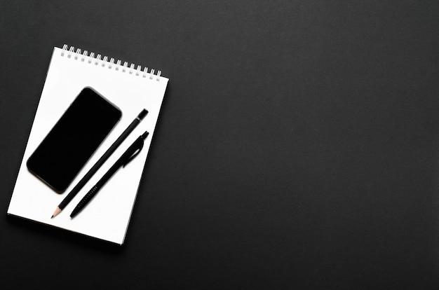 Белый открытый блокнот с черным карандашом, ручкой и смартфоном. офисный стол, канцтовары