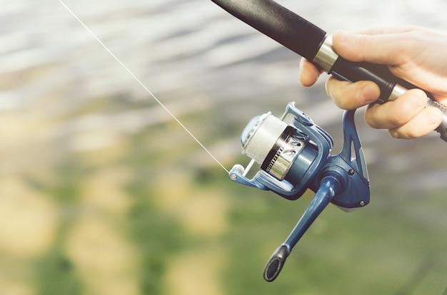 シャツを着た男性が青いリールで釣り竿を持っている
