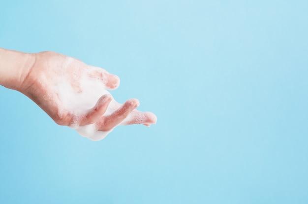 手は白い石鹸の泡で覆われています。手洗いと衛生。
