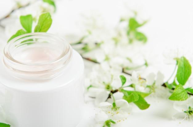 Крем для лица в белой баночке на белой поверхности с белыми мелкими цветками яблони.